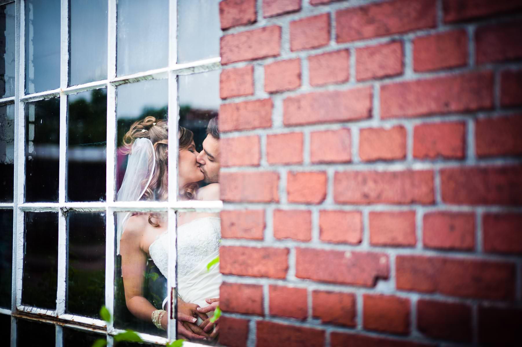 künstlerisches foto vom brautpaar durch ein gitterfenster