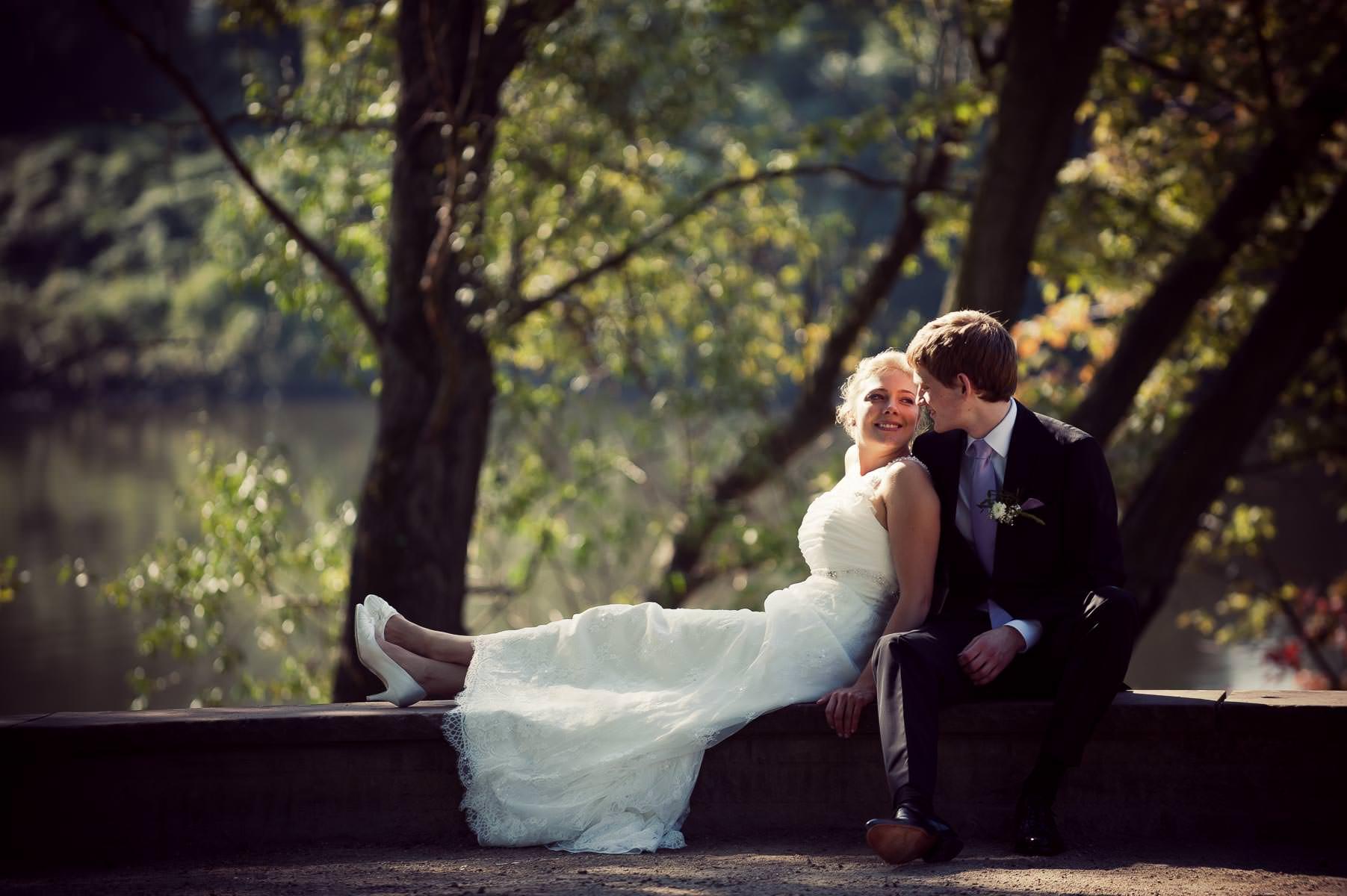 die Braut sitzt auf der Mauer und lehnt sich an den Bräutigam