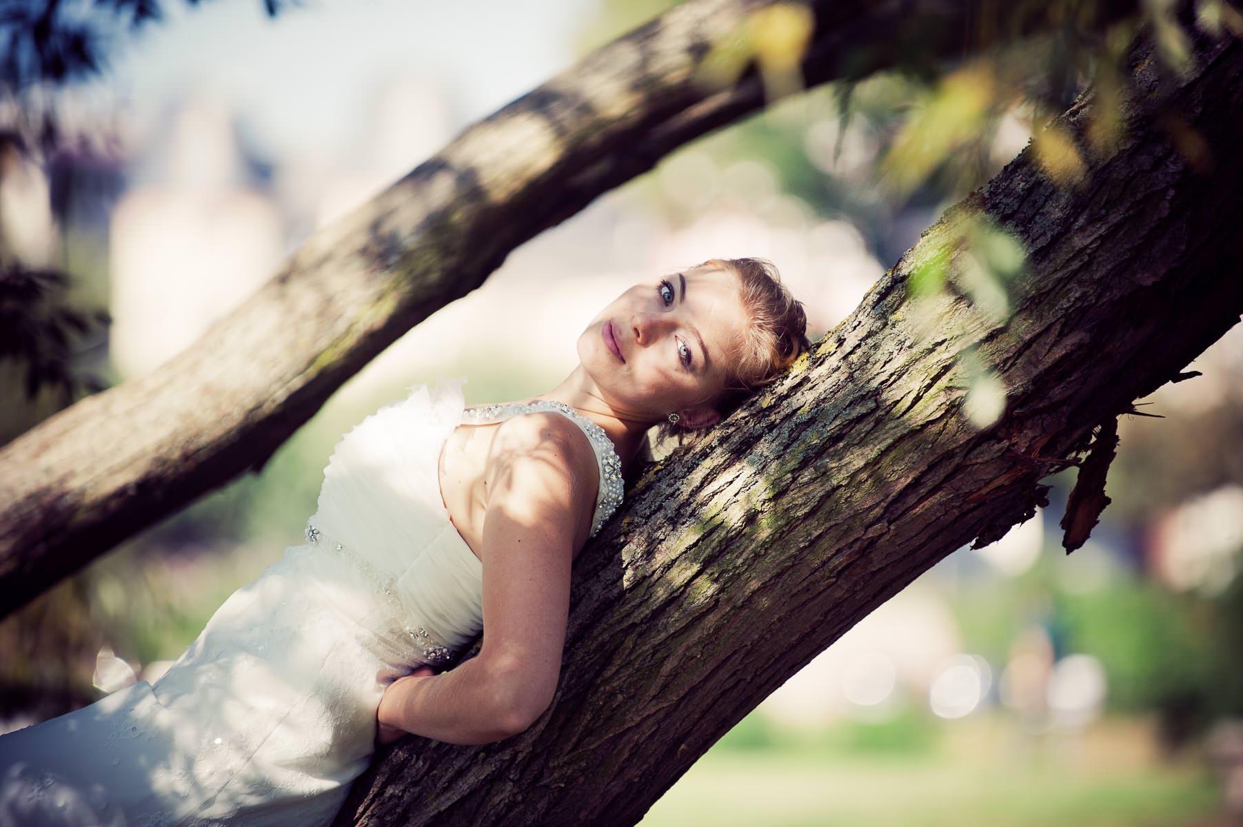 die Braut liegt auf dem Baumstamm