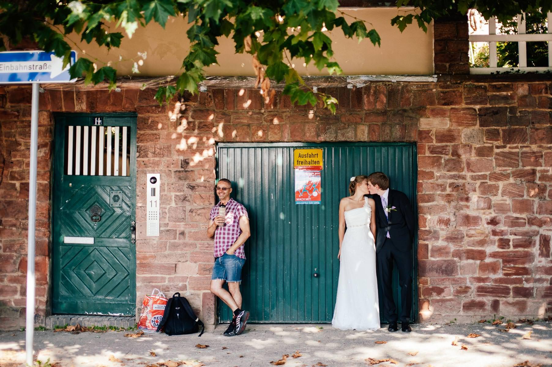 Brautpaar küsst sich angelehnt an eine Garagenwand. Ein Spazier