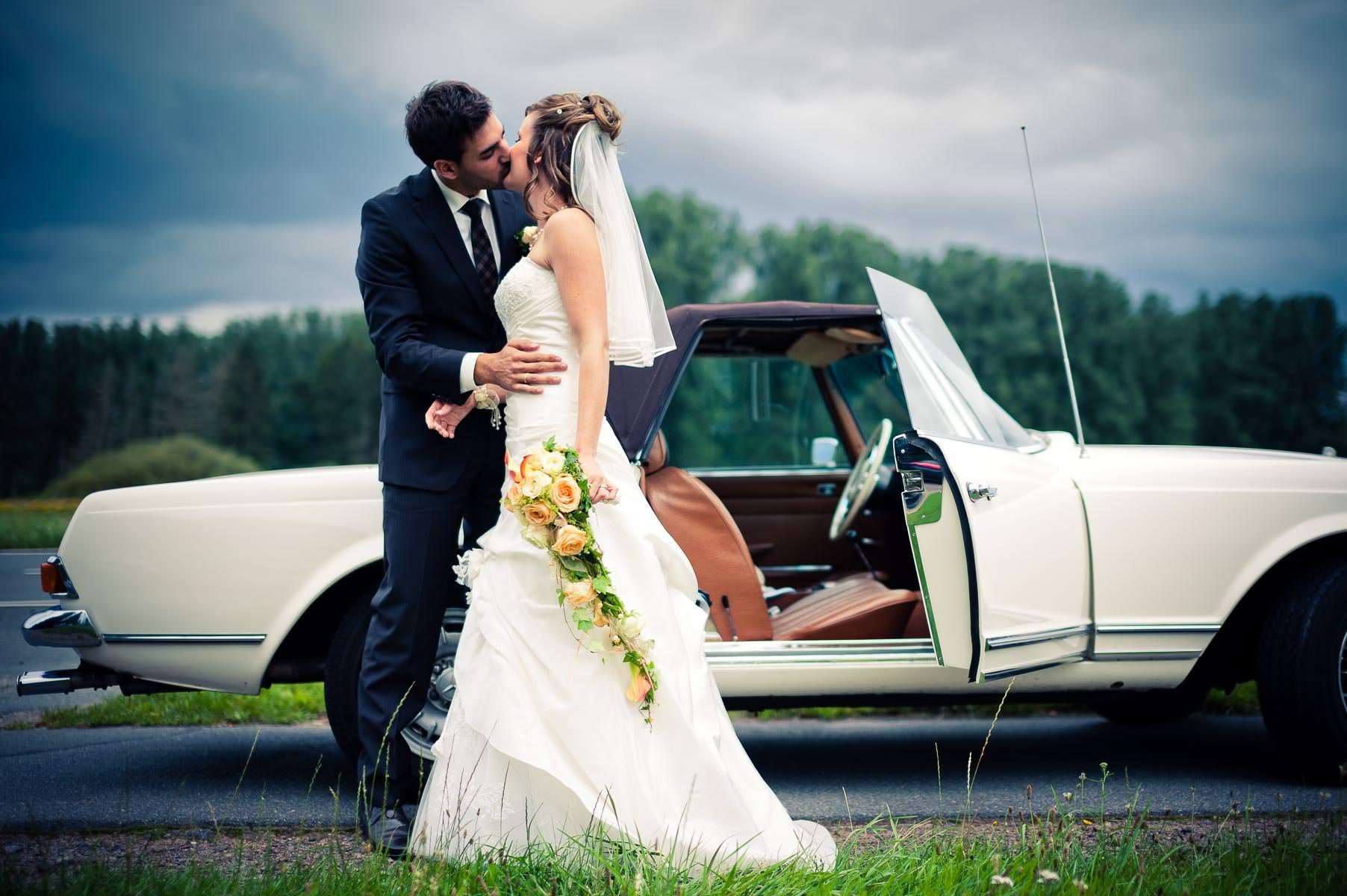 brautpaar küsst sich vor dem hochzeitsauto