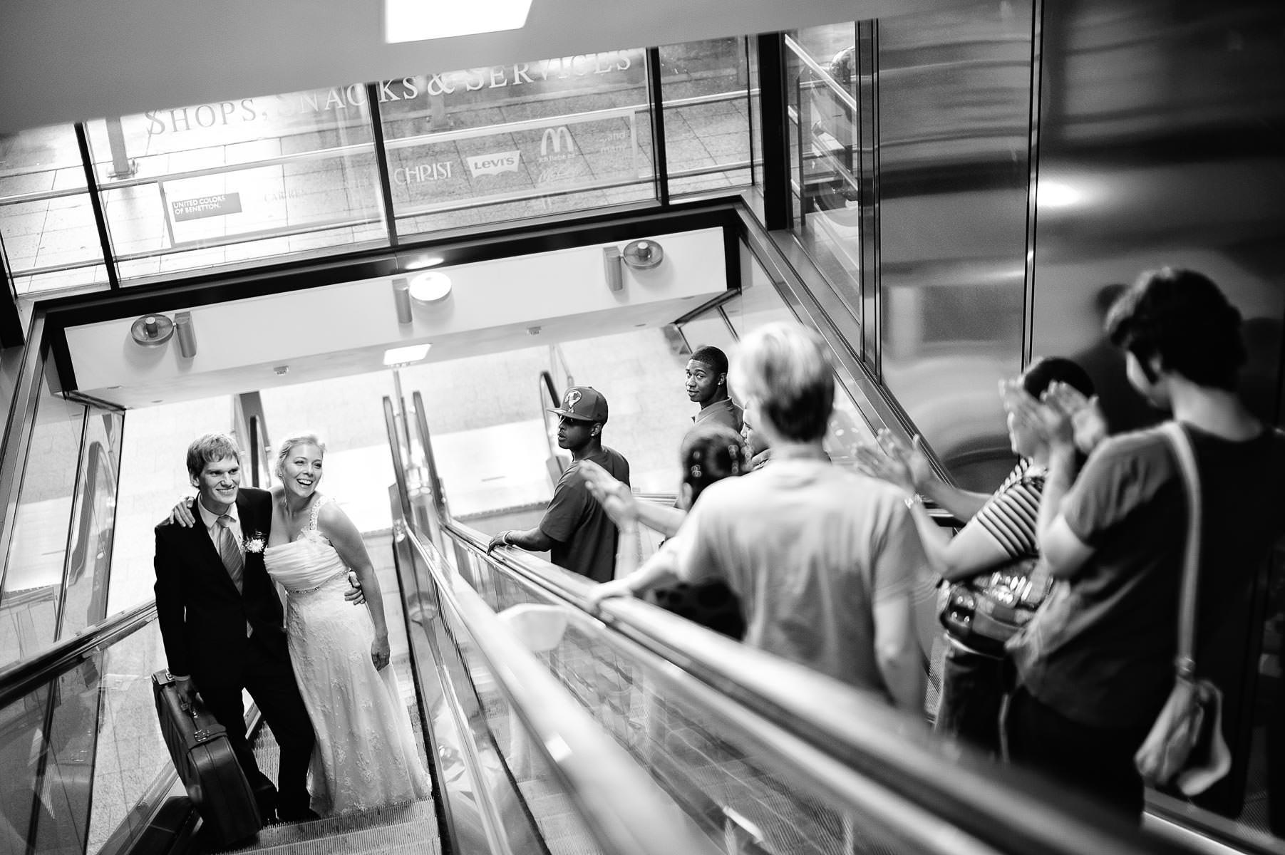 Brautpaar auf der Rolltreppe, sie lachen den entgegekommenden Pa