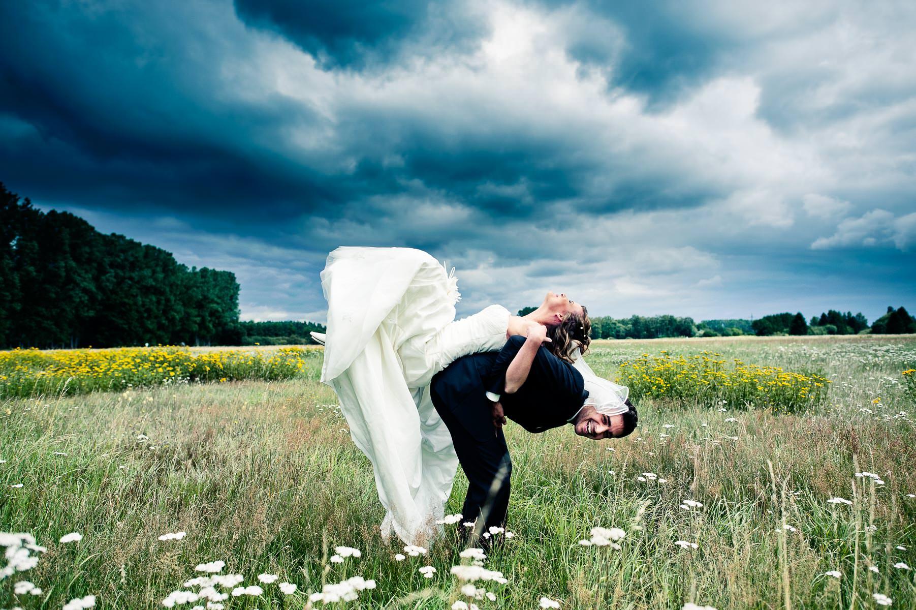 ein künstlerisches hochzeitsild von der braut, sie liegt auf dem rücken vom bräutigams