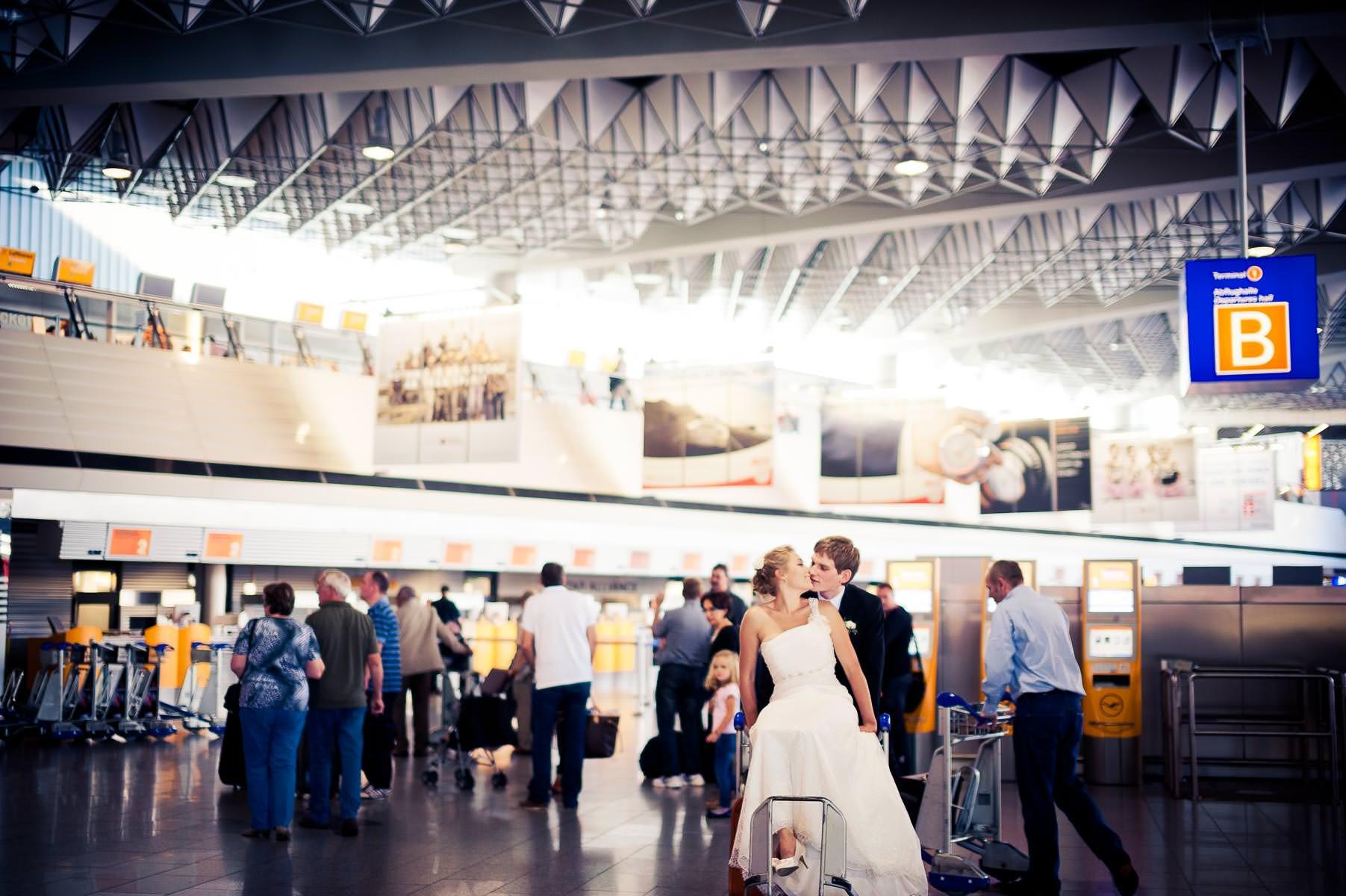 die Braut sitzt auf dem Kofferkuli und küsst den Bräutigam. Szenerie ist der Frankfurter Flughafen.