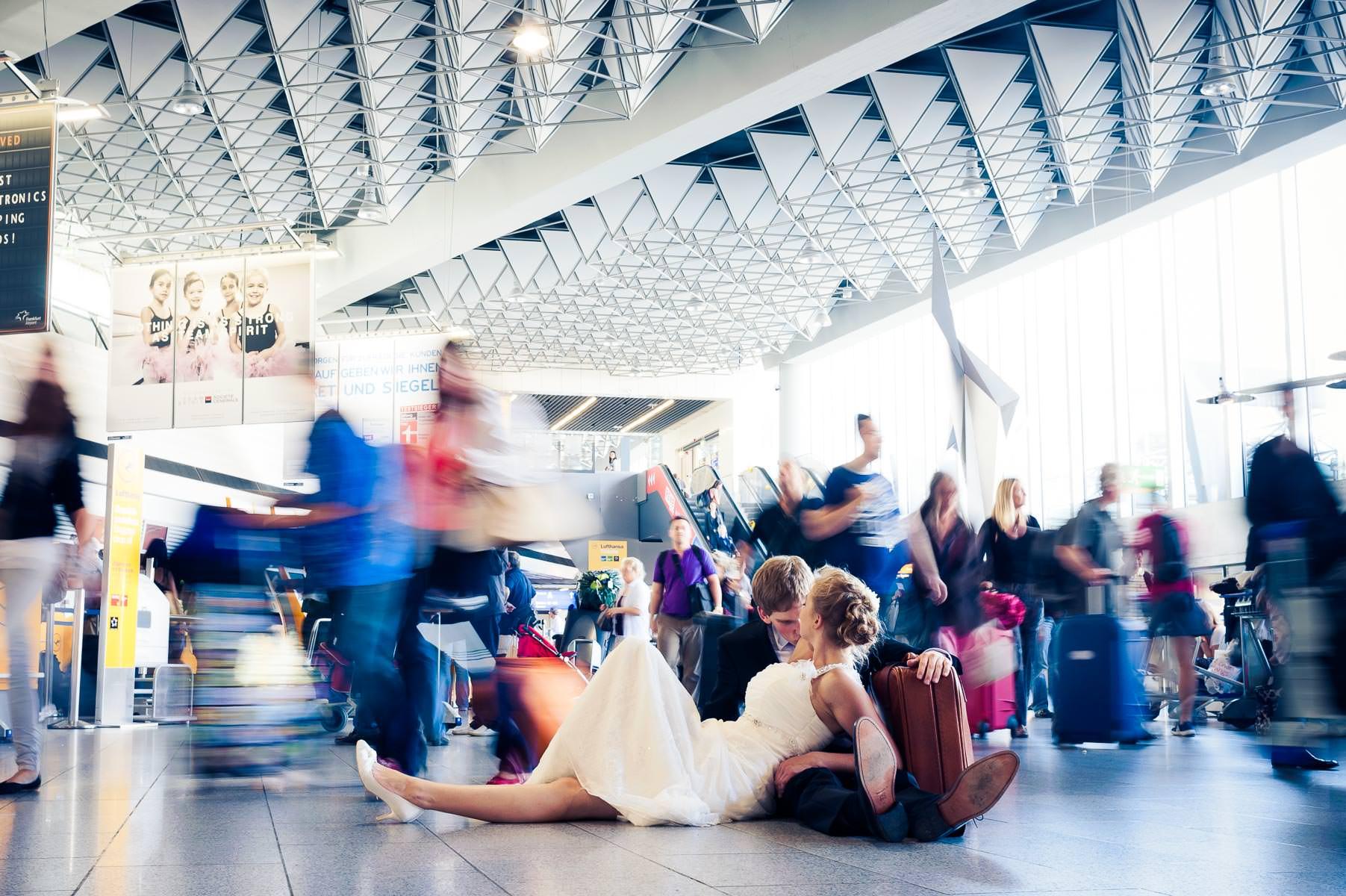 Brautpaar stzt auf dem Boden während um sie herum alle Passanten eilig laufen - das alles findet auf dem Flughafen in Frankfurt statt.