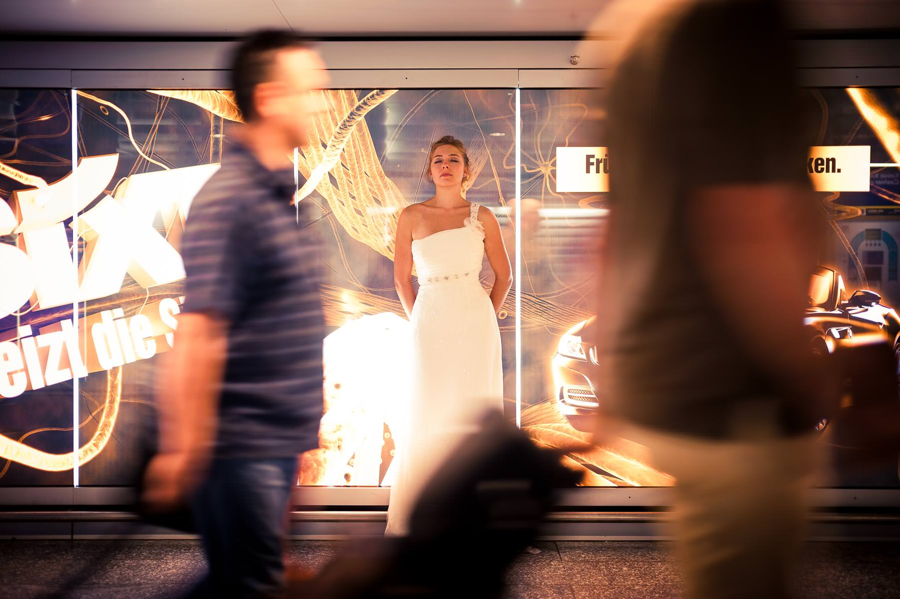 die Braut lehnt an der Leuchtreklame und genießt die Zeit während die Passanten eilig vorüberlaufen.