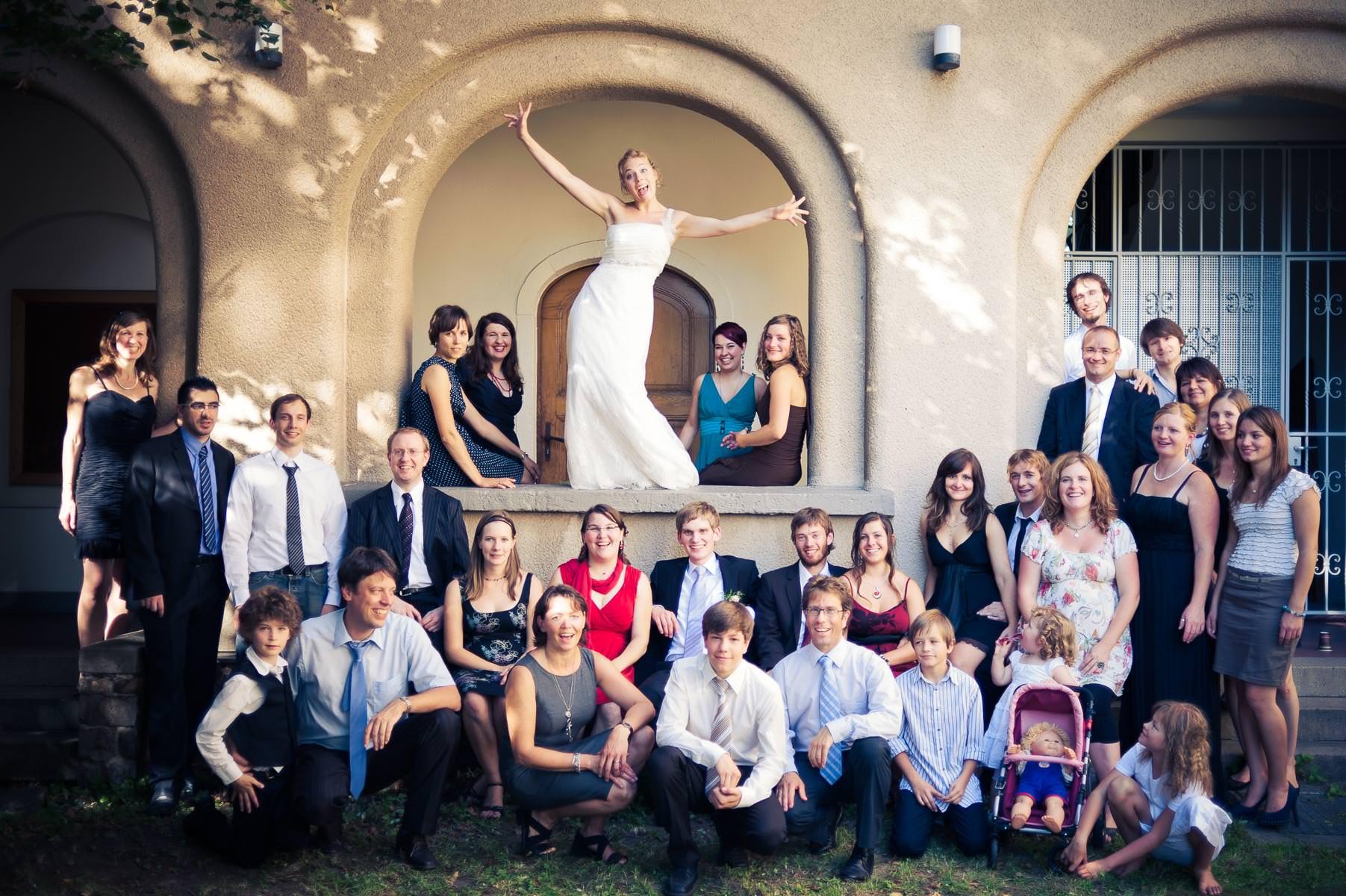 dynamisches gruppenbild auf der hochzeit, die Braut macht eine sportliche Bewegung während die Gesellschaft um sie herum sitzt