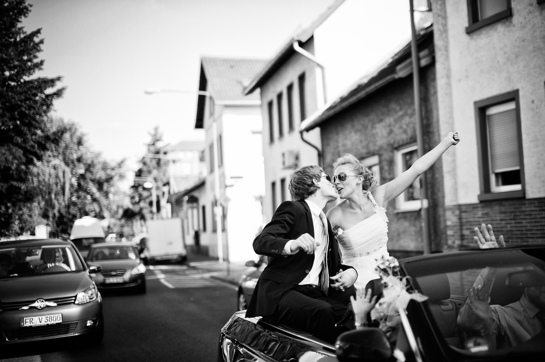 spannendes Bild vom Brautpaar, dass auf dem Verdeck des Cabrios