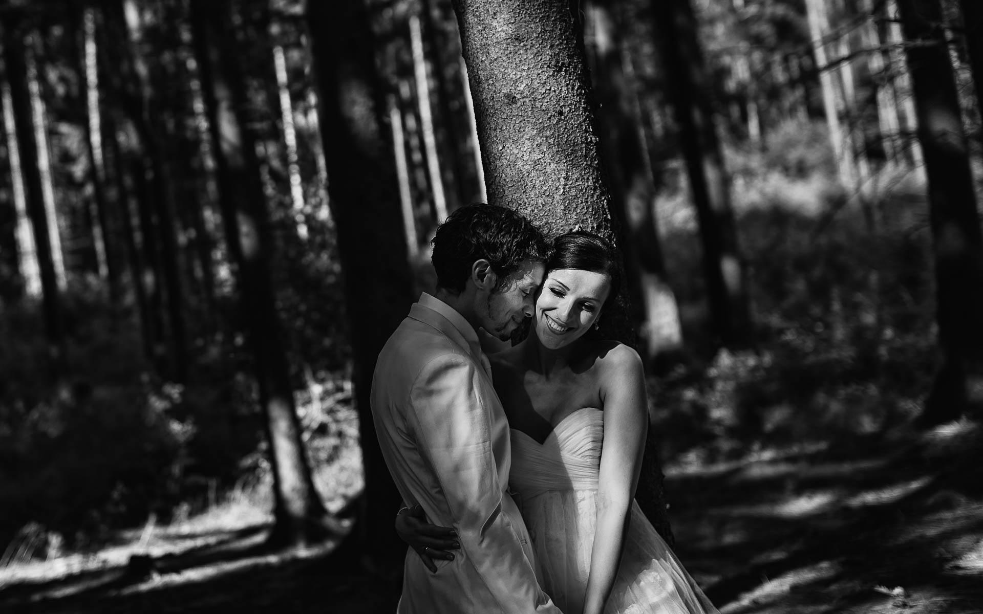 Braut und Bräutigam lachen vor Waldkulisse